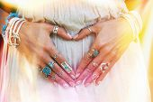 closeup of young woman hands in heart shape with lot of boho style jewrly, rings and bracelets outdo poster