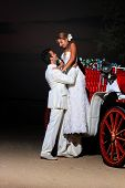 Beach wedding: bride and groom and a carriage by the sea