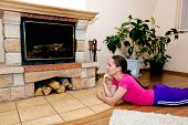 Beautiful girl warms by fireplace