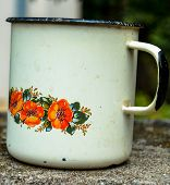 Retro Tea Cup Made From Tin Material.red An Orange Flower Pattern And Ornament Text.a Rusted Vintage poster