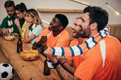 Side View Of Happy Young Multicultural Friends In Orange Fan T-shirts Celebrating Goal In Soccer Mat poster