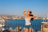 Beautiful Tourist Woman On The Old Castle On Mediterranean Sea Coast. Paphos, Cyprus. Bright Sunset  poster