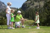 Outdoor photo of young family of four on golf course, father is instructing child.