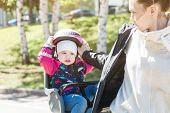 Portrait Of Little Girl With Security Helmet On The Head Sitting In Bike Seat And Her Mother With Bi poster
