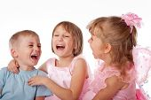 Three children joyfully laughing, studio, light background