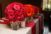 stock photo of flower vase  - Orange and pink Wedding flowers on the main table - JPG