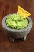A Photo Of Guacamole Sauce In A Molcajete, Traditional Mexican Mortar, On A Dark Rustic Texture With poster