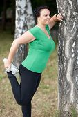 Happy Overweight Woman Stretching In The Woods. Selective Focus.