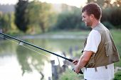 Happy Man Fishing In A Pond. Shallow Dof.