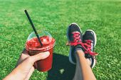 Girl drinking red beet or fruit smoothie plastic cup during fitness workout. Healthy detox juice wom poster