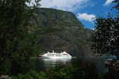 Cruise Ship In Sea Harbor With Green Mountains In Flam, Norway. Ocean Liner In Sea Port On Mountain  poster