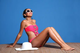 stock photo of monokini  - Long legged young african american woman wearing pink monokini swimsuit sitting on bamboo mat sun tanning with head back and eyes closed - JPG
