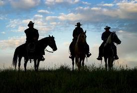stock photo of wild west  - Cowboys on horseback at first light - JPG
