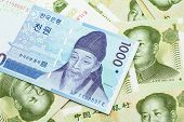 A Blue South Korean One Thousand Won Bank Note Close Up In Macro On A Background Of Chinese One Yuan poster