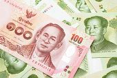A Close Up Image Of A Red, One Hundred Baht Note From Thailand With Chinese One Yuan Bills In Macro poster
