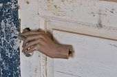 foto of mutilated  - Detached mannequin doll hand pulling old door handle in haunted house - JPG