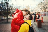 Young Romantic Couple In Love Kissing, Hugging, Wearning In Bright Yellow And Red Down Jackets. Hand poster