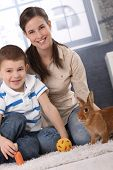 Happy mum and little son playing with domestic rabbit at home, carrot and ball. poster