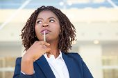 Pensive Young Businesswoman Holding Pen. Low Angle View Of Thoughtful African American Businesswoman poster