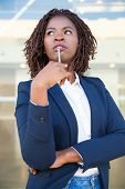 Thoughtful Young Businesswoman Holding Pen. Low Angle View Of Pensive African American Businesswoman poster