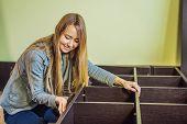 Caucasian Woman Using Screwdriver For Assembling Furniture poster