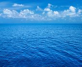 Sea and blue sky. Blue sea water and  sky with white fluffy clouds. Horizontal background of blue se poster
