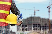 man holding yellow helmet in front of construction site