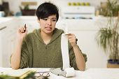 Mixed Race Young Female Agonizing Over Financial Calculations in Her Kitchen.