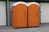 stock photo of porta-potties  - Two orange porta potty toilets ready for sanitary use at an event - JPG