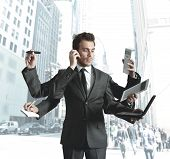 stock photo of multitasking  - A businessman stressed by too many tasks - JPG