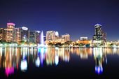 Orlando downtown skyline panorama over Lake Eola at night with urban skyscrapers, fountain and clear