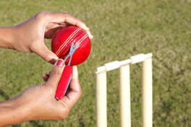 stock photo of umpire  - Umpire Repairing The Cricket Ball With The Help Of Pocket Scissor - JPG