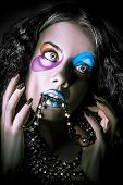 picture of jester  - Dark closeup portrait of a beautiful high fashion female jester wearing colorful cosmetics with jewellery chain hanging from bright blue lips - JPG