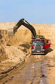 stock photo of dumper  - Excavator Loading Dumper Truck at Construction Site - JPG
