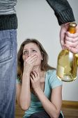 Home Violence Concept. Frightened Woman And Male Hand Holding Bottle Of Wine