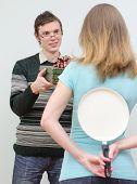 Woman Hiding Pan Underhand Talking To Man