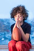 Young Hispanic Child Praying So The Weather Improves And He Can Go To Play Outdoors