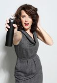 stock photo of hairspray  - Beautiful girl laying fixes using hairspray  - JPG