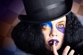 stock photo of mad hatter  - Face portrait of a female mad hatter wearing black top hat bright colourful makeup with black manicured nails - JPG