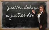 Teacher Showing Justice Delayed Is Justice Denied On Blackboard