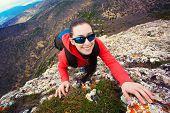 woman climber is climbing on a rock