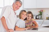 Grandfather and children looking at the camera together with laptop in front in kitchen