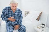Aged man suffering with belly pain