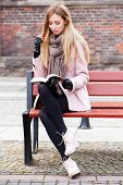 Gorgeous blonde reading a book in the street