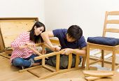 Asian couple assembling new chair