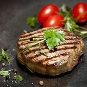 Grilled steak with herbs and tomatoes, on dark slate.
