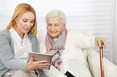 Woman giving senior woman introduction to internet with a tablet computer