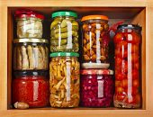 stock photo of pickled vegetables  - many glass bottles stack with preserved food in wooden cabinet - JPG