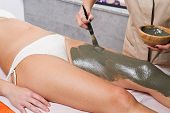 Relaxing Woman Lying On A Massage Table Receiving A Mud Treatment