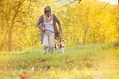 stock photo of dog-walker  - Senior woman walking her beagle dog in countryside